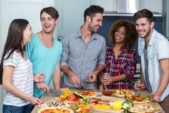Amis multi-ethniques gais préparant la pizza à la maison Photos libres de droits