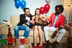 Amis multi-ethniques grillant avec de l'alcool Photographie stock