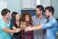Amis multi-ethniques grillant la bière et le vin dans la cuisine Images libres de droits