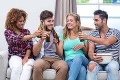 Amis multi-ethniques grillant la bière tout en se reposant sur le sofa Photo stock