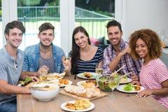 Amis multi-ethniques heureux ayant le repas à la table Photographie stock
