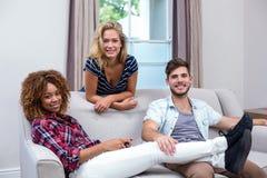 Amis multi-ethniques heureux détendant au sofa Photographie stock libre de droits