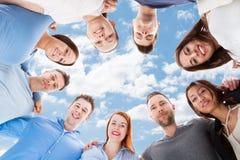 Amis multi-ethniques heureux formant le petit groupe contre le ciel Image libre de droits