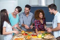 Amis multi-ethniques heureux préparant la pizza à la maison Image libre de droits