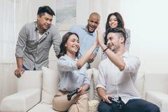 Amis multi-ethniques jouant des jeux vidéo et donnant la haute cinq à la maison Images stock