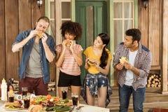 Amis multi-ethniques mangeant des hamburgers au pique-nique sur le patio Image libre de droits