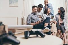 Amis multi-ethniques occasionnels passant le temps ensemble tout en se reposant sur le sofa à la maison Photo stock