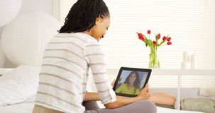 Amis multi-ethniques parlant en ligne avec le comprimé Image stock