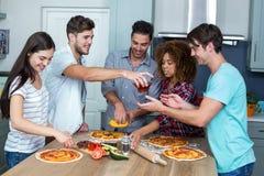 Amis multi-ethniques préparant la pizza sur la table de cuisine Image libre de droits