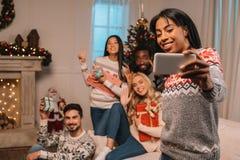 Amis multi-ethniques prenant le selfie sur Noël Photos stock