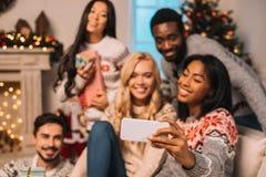 Amis multi-ethniques prenant le selfie sur Noël Photographie stock