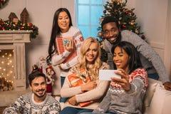 Amis multi-ethniques prenant le selfie sur Noël Photo stock