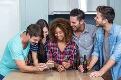 Amis multi-ethniques regardant dans le téléphone portable à la maison Photo libre de droits