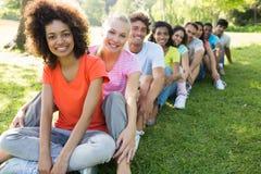 Amis multi-ethniques s'asseyant dans une ligne Photo stock
