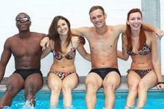Amis multi-ethniques s'asseyant du côté de la piscine Images libres de droits