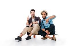 Amis multi-ethniques s'asseyant sur la planche à roulettes avec des gestes de main d'isolement sur le blanc Photo libre de droits