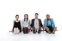 Amis multi-ethniques s'asseyant sur le plancher et regardant l'appareil-photo Images stock