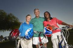 Amis multi-ethniques se tenant avec des bicyclettes Photo libre de droits