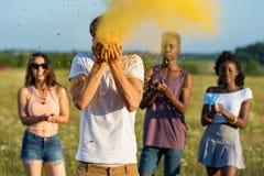 Amis multi-ethniques soufflant la poudre des paumes au festival de holi Image stock