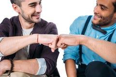 Amis multi-ethniques souriant et faisant la bosse de poing d'isolement sur le blanc Photos stock