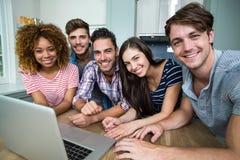 Amis multi-ethniques souriant tout en à l'aide de l'ordinateur portable sur la table Images libres de droits