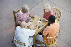 Amis multi-ethniques supérieurs jouant des cartes ensemble Image libre de droits