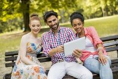 Amis multi-ethniques sur le banc en parc Photo libre de droits