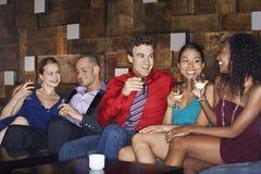 Amis multi-ethniques sur le divan avec des boissons Photographie stock