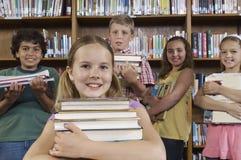 Amis multi-ethniques tenant la pile de livres Images libres de droits
