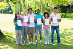 Amis multi-ethniques tenant les papiers blancs Photo libre de droits
