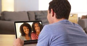 Amis multi-ethniques webcamming sur l'ordinateur portable Photographie stock libre de droits