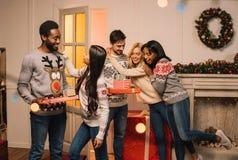 Amis multiculturels échangeant des cadeaux de Noël Photographie stock libre de droits