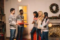 Amis multiculturels échangeant des cadeaux de Noël Photo libre de droits