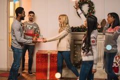 Amis multiculturels échangeant des cadeaux de Noël Photos stock