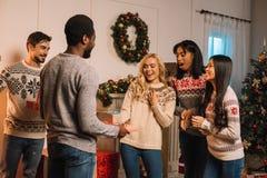 Amis multiculturels échangeant des cadeaux de Noël Images stock