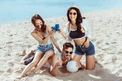 Amis multiculturels avec des boîtes de boule et de soude de volleyball se reposant sur la plage sablonneuse Photographie stock libre de droits