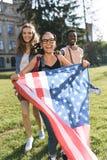 Amis multiculturels avec le drapeau américain Images libres de droits