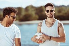 Amis multiculturels dans des lunettes de soleil tenant la boule de volleyball sur la rive Photographie stock libre de droits