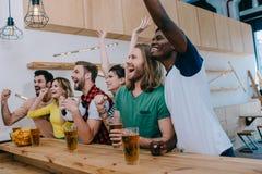 amis multiculturels enthousiastes célébrant faire des gestes à la main et observant le match de football image stock