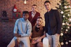 Amis multiculturels se reposant ensemble à la maison le réveillon de Noël Photos stock