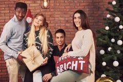Amis multiculturels se reposant ensemble à la maison le réveillon de Noël Photographie stock