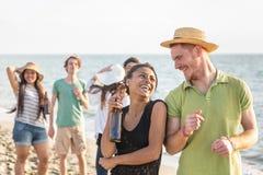 Amis multiraciaux à la plage Photographie stock