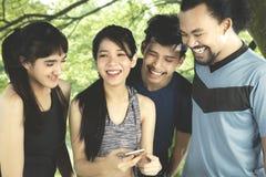 Amis multiraciaux avec le téléphone portable au parc Images libres de droits