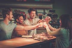 Amis multiraciaux ayant l'amusement mangeant dans la pizzeria Photographie stock libre de droits