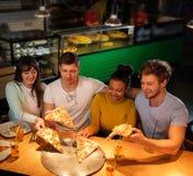 Amis multiraciaux ayant l'amusement mangeant dans la pizzeria Images libres de droits