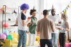 Amis multiraciaux célébrant l'anniversaire avec des boissons image stock