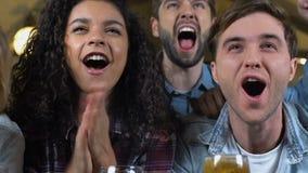 Amis multiraciaux célébrant le but préféré d'équipe de sports dans le bar, championnat clips vidéos