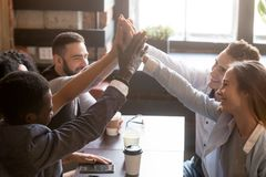 Amis multiraciaux donnant la haute cinq se reposant dans le café Images libres de droits