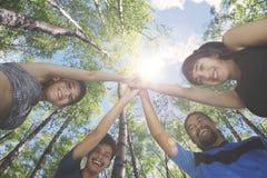 Amis multiraciaux faisant la haute cinq dehors Photographie stock