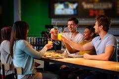 Amis multiraciaux gais ayant l'amusement mangeant dans la pizzeria Images stock